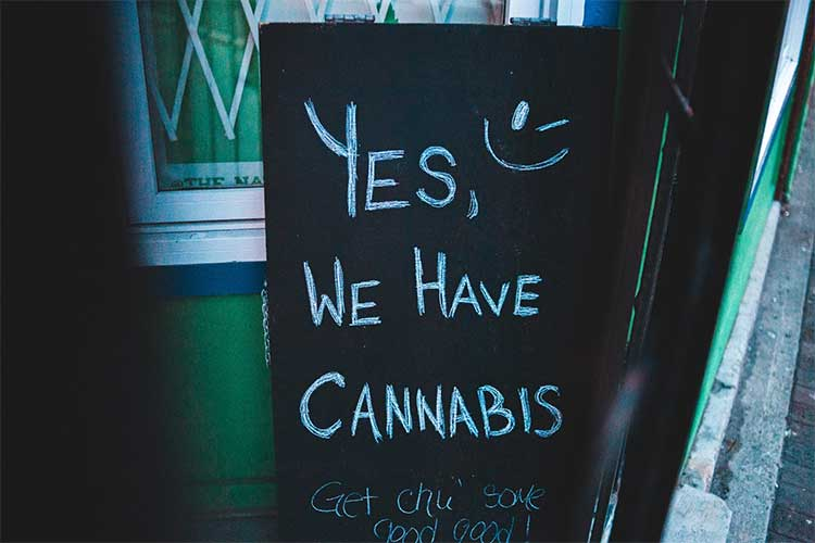 Sign outside a dispensary that says Yes, we have cannabis.